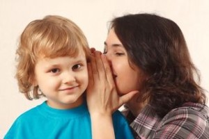 parent whispering in child's ear